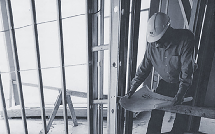 photo showing builder looking at plans in a commercial building